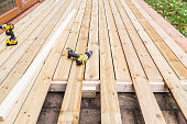 A new wooden, timber deck being constructed. it is partially completed. two drill can be seen on the decking.