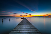 Wooden Dock and fishing boat at the lake, city lights at sunset