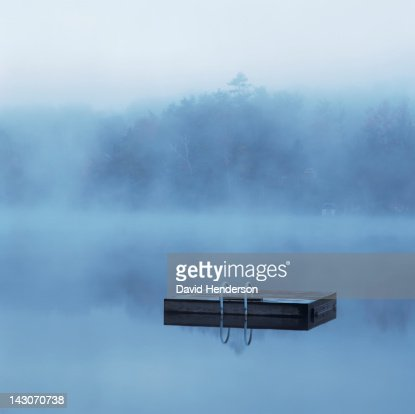 Wooden dock floating in still lake : Stock Photo