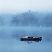 Wooden dock floating in still lake