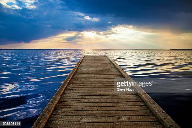 A Wooden Dock Leads Out To Gull Lake With The Sunlight Reflecting On The Water At Sunset; Alberta Canada