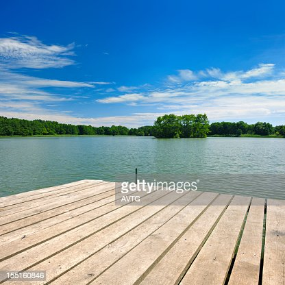 Hölzerne Dock auf dem See unter den Wald unter bewölkten Himmel