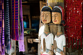 Wooden Dolls of Karen long neck hill tribe, the village in north of Thailand, acting as welcome to visit.