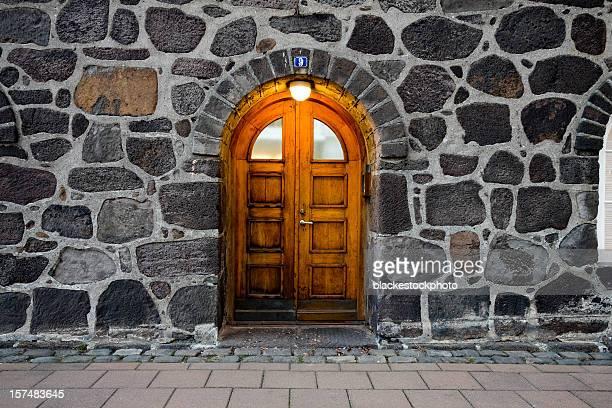 Wooden door in illuminated doorway, set within stone wall