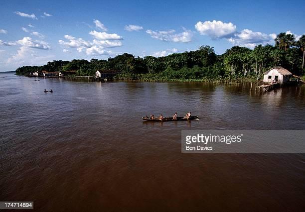 AMAZON SANTAREM PARA BRAZIL A wooden dugout filled with children paddles across the Amazon River through the lush rain forest of Brazil near Santarem...
