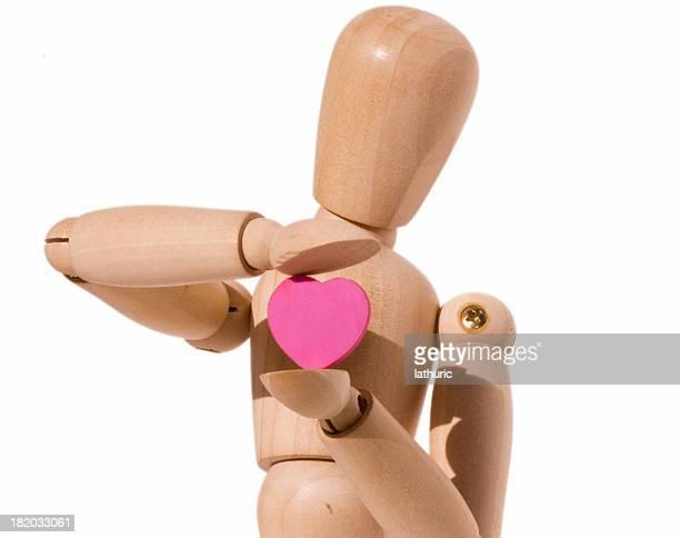 Manichino che tiene un cuore in legno