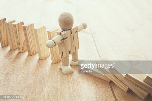 A wooden dummy stopping the domino effect. retro style image executive and risk control concept. : Stock Photo