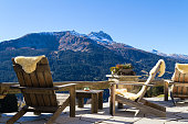Wooden easy chairs at a mountain lodge terrace with panoramic view of beautiful alpine landscape in autumn at the Klosters - Davos region, Switzerland.