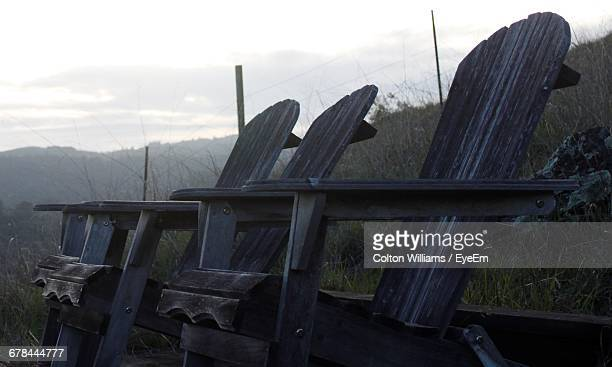 Wooden Empty Chairs On Field Against Sky