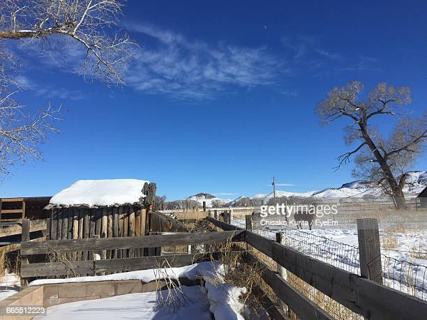 Wooden Fence By Snow Covered Field Against Sky