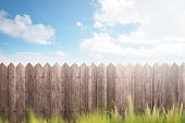 Wooden fence on green garden against blue sky background