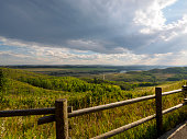 A wooden fence that overlooks the plains and valleys of a ranch in Alberta as rain clouds blow in