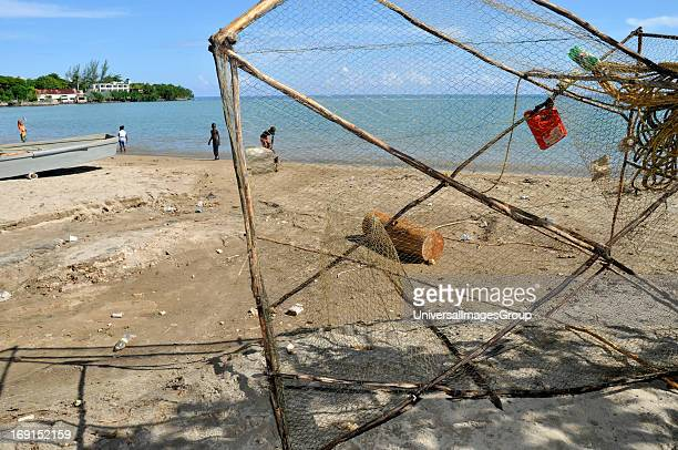 A wooden frame wire net fish trap sits on the beach in Rio Bueno Jamaica Children can be seen in the distance