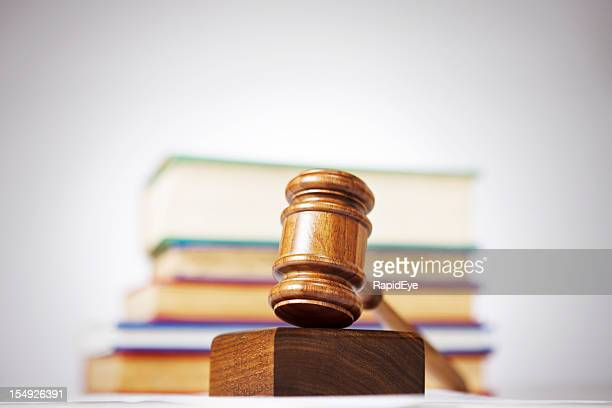 Wooden gavel with law books in background: justice theme