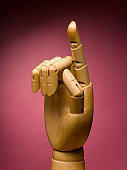Wooden hand with index finger extended, close-up