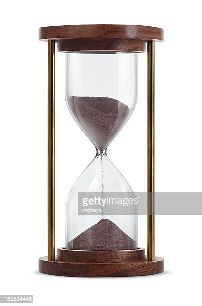 Wooden hourglass with brown sand running through it