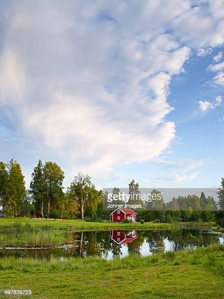 Wooden house reflecting in water, Vastergotland, Sweden