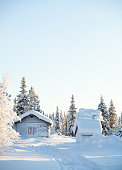 Winter landscape with an wooden hut. Sunny bright day in Swedish Lapland.