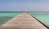 Wooden jetty and turquoise water of Indian ocean in Maldives