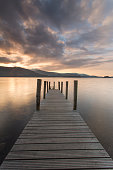 Wooden jetty at sunset, looking out to Catbells mountain in the lake district.