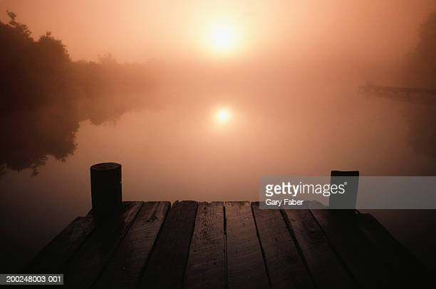 Wooden jetty on lake at sunset, New Orleans, LA, USA