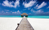 Wooden jetty to a water lodge on a tropical beach with white sand and turquoise waters