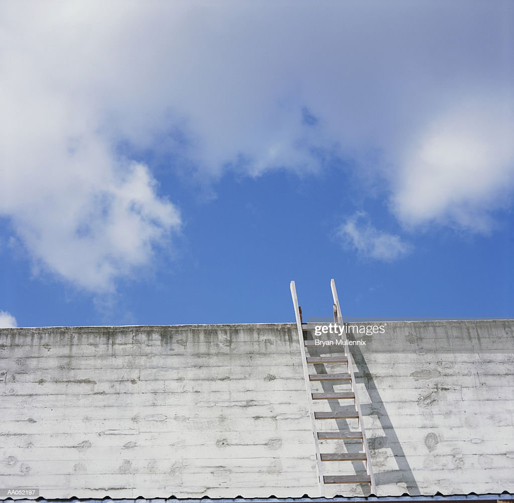 Wooden ladder against brick wall leading to blue cloudy skies : Stock Photo