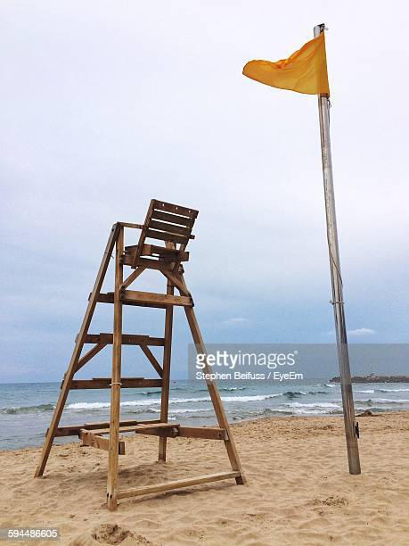 Wooden Ladder On Beach By Sea Against Sky