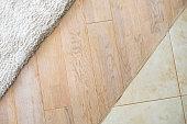 Laminate parquete floor.  Beige soft carpet. Marble tile. Warm interior design