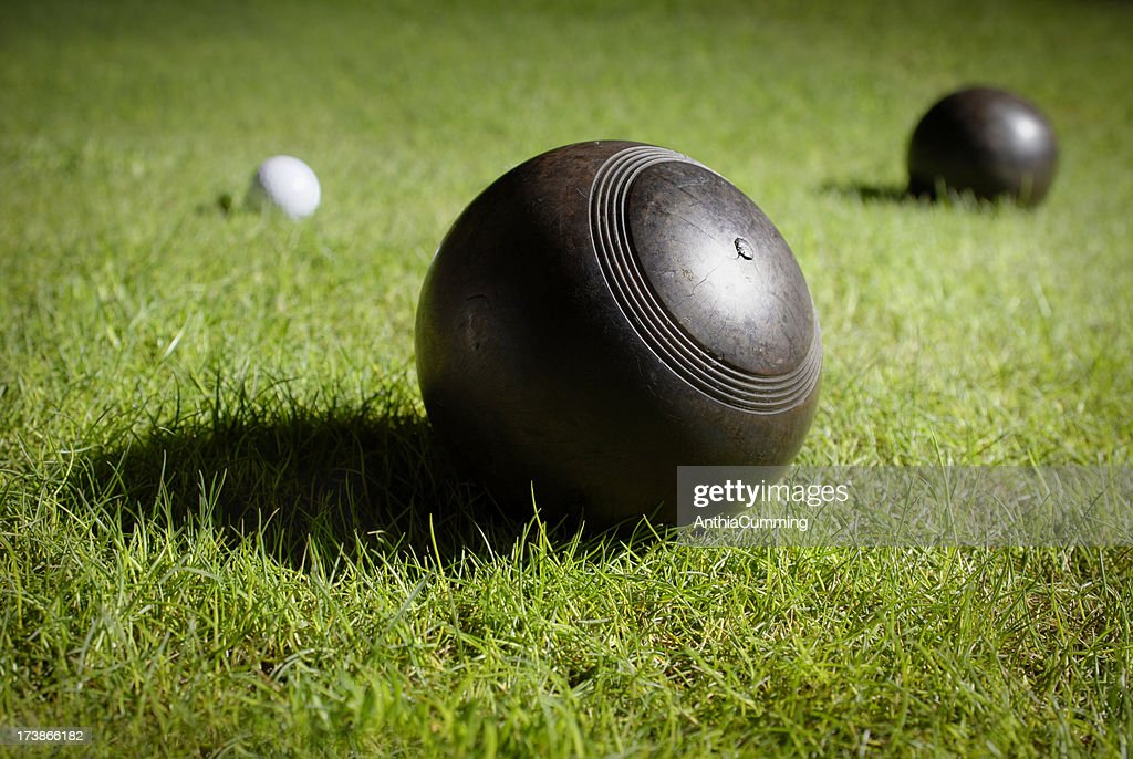 Wooden lawn bowls on a bowling green around jack