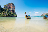 In Railay Beach a traditional wooden boat, called a longtail boat, is tied up along the Adaman Sea in the Krabi province of Thailand, a Southeast Asia travel destination. The horizon is seen over wate
