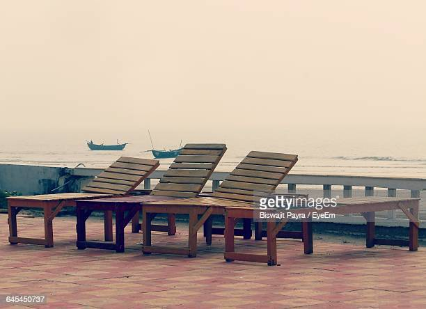 Wooden Lounge Chairs On Promenade Against Clear Sky