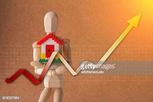 wooden man holding home model with growth graph analysis.jpg : Stock Photo