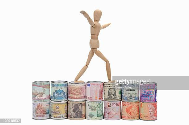 Wooden mannequin balancing on worldwide banknotes