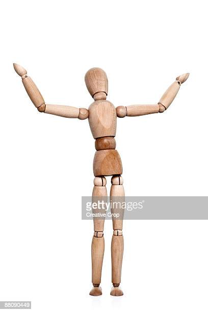Wooden mannequin stood with arms in the air