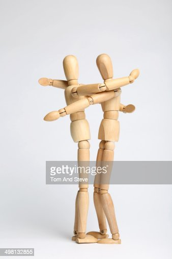 Wooden mannequins embracing in a hug