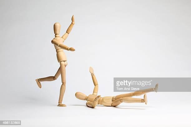 Wooden mannequins fighting