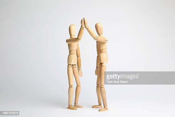 Wooden mannequins high five
