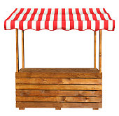This is an empty wooden stall stand with red white awning.