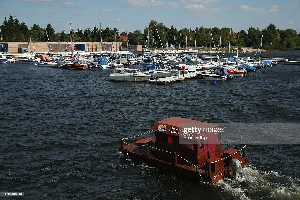 A wooden, motorized raft carrying tourists arrives at the marina of artificial Senftenberger See lake on August 26, 2013 in Senftenberg, Germany. Senftenberger See was once an open-pit lignite coal mine flooded after it shut down in the late 1960s, and today it is popular among tourists, windsurfers and fishermen. In a development project initiated by state government, other nearby former open-pit mines that once evoked a lunar landscape are being turned into lakes in a long-term rejuvenation effort that is also intended to make the area a viable tourist destination. Mineral residue from the mines, however, is proving a difficult stumbling block that is making many of the new lakes too acidic to sustain marine life in the short term.