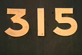 Wooden number glued on surface