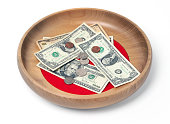 Wooden offering plate with paper bills and coins
