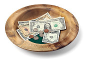 Wooden offering bowl with paper bills and coins