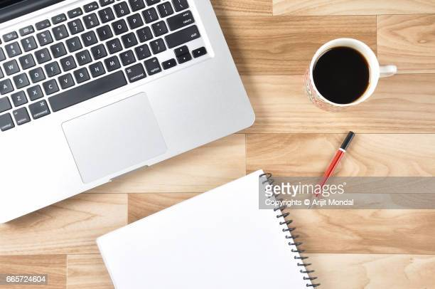 Wooden Office Desk Top View with Laptop, Black Tea, Notepad in Retro Style