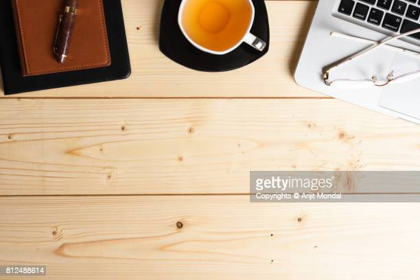 Wooden office table top view shot with notepad, laptop, eye-wear and tea cup