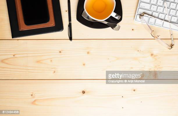 Wooden office table top view with notepad, tea with cup and plate, computer keyboard and copy space