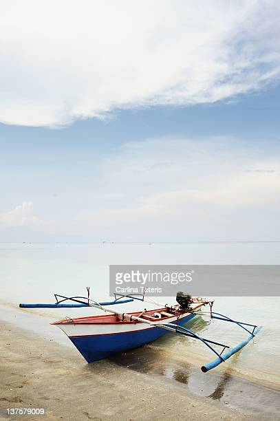 Wooden outrigger boat on shore