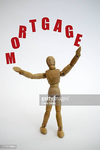 Wooden person Juggling with Mortgage.