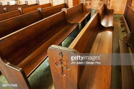 Wooden pews in a church with crosses etched into the ends