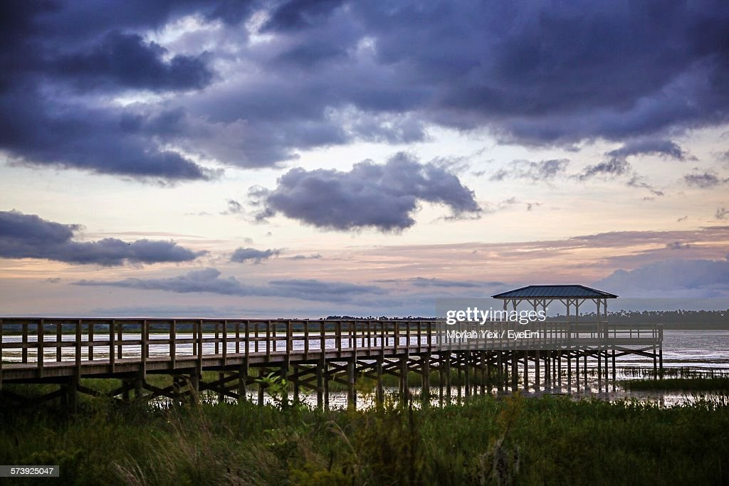 Wooden Pier Against Cloudy Sky During Sunset